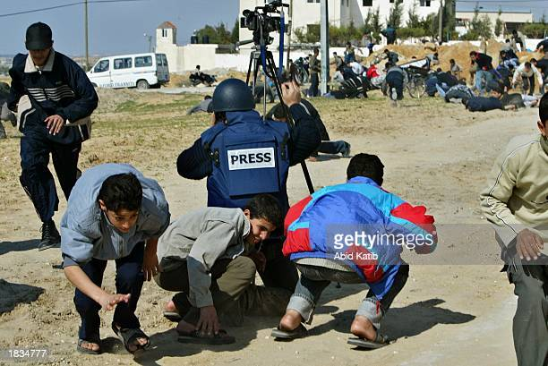Palestinians and a television cameraman take cover as an Israeli tank opens fire during clashes March 7 2003 in Beit Lahyea in the Gaza Strip About...