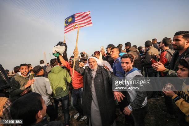 Palestinians are seen as Israeli forces intervene them with tear gas canisters during a Great March of Return demonstration in Khan Yunis Gaza on...