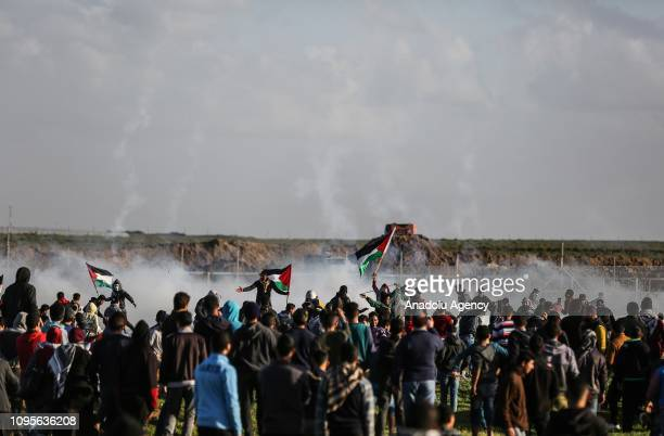 Palestinians are seen as Israeli forces intervene them with tear gas canisters during a Great March of Return demonstration on Israeli Border of...