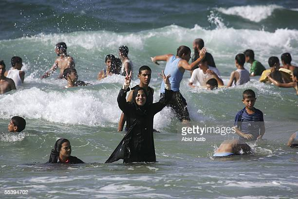 Palestinians are seen in the water on the beach September 13 2005 near the former Israeli settlement of Neve Dekalim Thousands of residents of the...