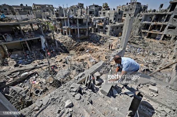 Palestinians assess the damage caused by Israeli air strikes, in Beit Hanun in the northern Gaza Strip, on May 14, 2021. - Israel pounded Gaza and...