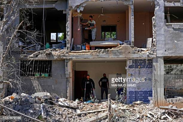Palestinians assess the damage in a building caused by Israeli air strikes, in Beit Hanun in the northern Gaza Strip, on May 14, 2021. - Israel...
