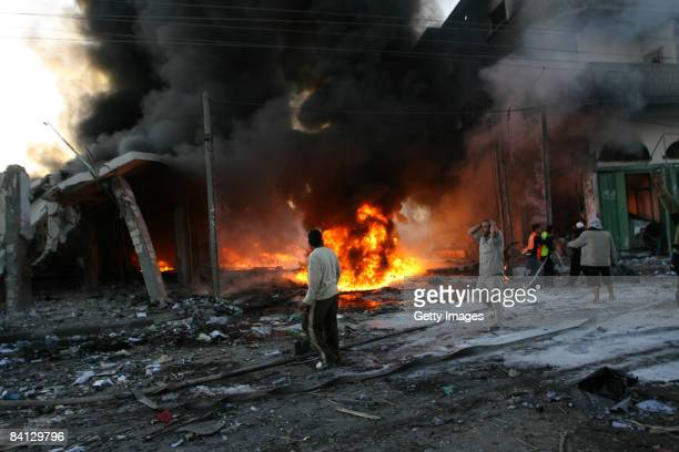 Palestinians attempt to douse flames at the site of an Israeli air strike on December 28, 2008 in Rafah, Gaza. Israel has launched further air...