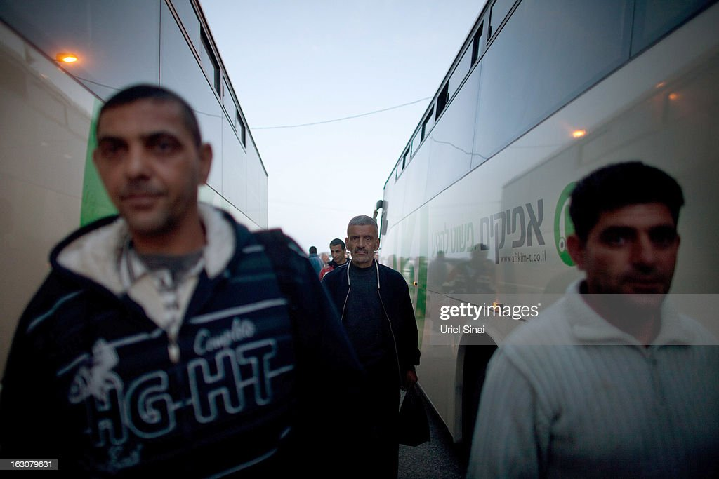 Palestinians board a bus as a new line is made available by Israel to take Palestinian labourers from the Israeli army crossing of Eyal, near the West Bank town of Qalqilya, into the Israeli cities, on March 4, 2013. at Eyal crossing, West Bank.The new line service to ferry Palestinian workers from the West Bank to Israel, encouraging them to use it instead of traveling with Israeli settlers on a similar route.