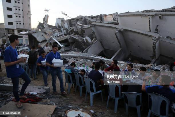 Palestinians break their fast by eating the Iftar meals during the holy month of Ramadan near the rubble of a building recently destroyed by Israeli...