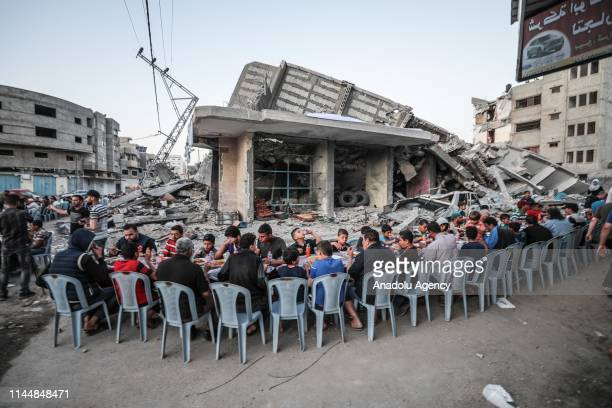 Palestinians break their fast during a fast-breaking dinner amongst rubble of houses in Gaza City, Gaza on May 18, 2019.