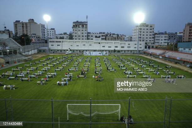 Palestinians break their Ramadan fast during an Iftar meal set-up to respect social distancing measures amid the COVID-19 pandemic, organized by the...