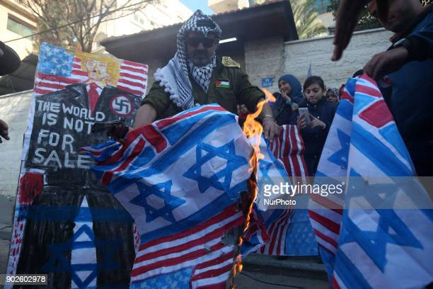 Palestinians burn an Israeli flag and a US flag during a protest to show solidarity with Palestinian prisoners held in Israeli jails in front of Red...