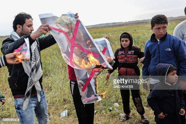 Palestinians burn crossedout posters depicting Israeli Prime Minister Benjamin Netanyahu and US President Donald Trump during a tent city protest...
