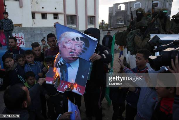 Palestinians burn posters of Israeli Prime Minister Benjamin Netanyahu and US President Donald Trump during a protest against the US decision to...