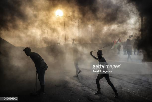 Palestinians burn tires and use slingshots to throw rocks in response to Israeli intervention during a Great March of Return demonstration at Beit...