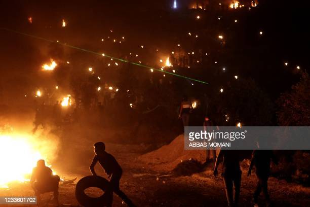 Palestinians burn tires during a night demonstration against the expansion of the Jewish settlement outpost of Eviatar, on the lands of Beita...