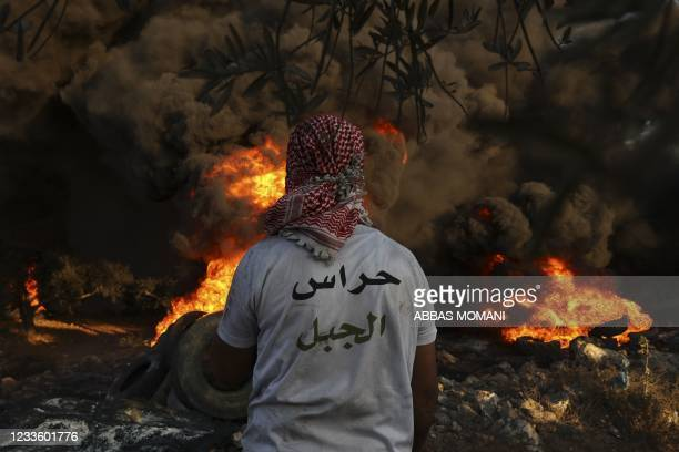 Palestinians burn tires during a night demonstration against the expansion of the Jewish settlement outpost of Eviatar on the lands of Beita village,...