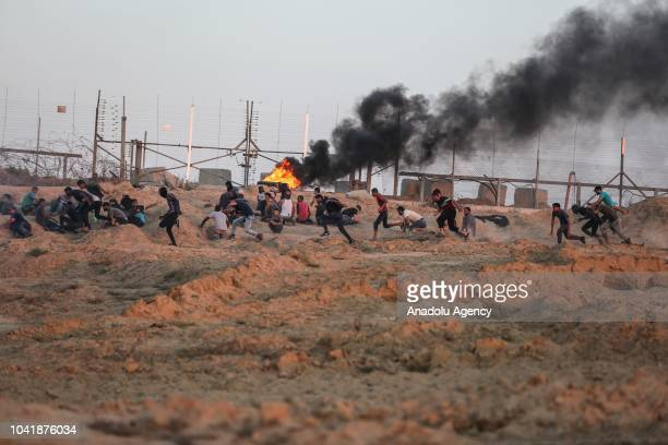 "Palestinians burn tires in response to Israeli intervention during the ""Great March of Return"" demonstration at the Israeli border in eastern Deir Al..."