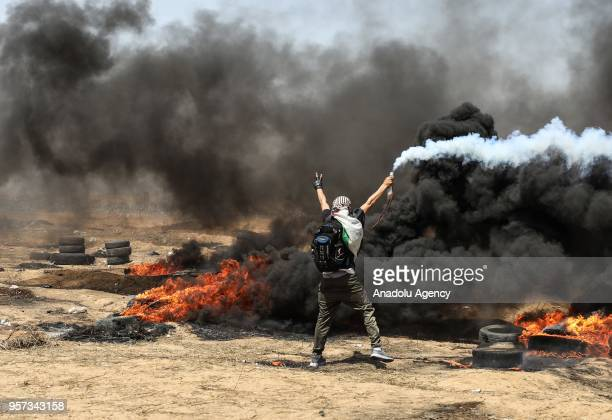 Palestinians burn tyres in response to Israeli forces' intervention during a demonstration within the Great March of Return near Israeli border in...