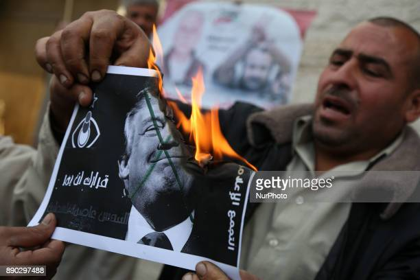 Palestinians burns a poster depicting U.S. President Donald Trump during a protest against Trump's decision to recognize Jerusalem as the capital of...