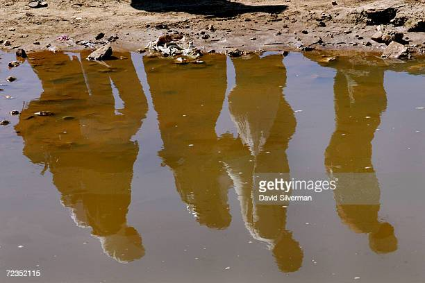 Palestinians bypassing an Israeli army roadblock are reflected in a pool of rainwater February 20, 2002 on the outskirts of the West Bank town of...