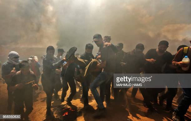 TOPSHOT Palestinians carry a demonstrator injured during clashes with Israeli forces near the border between the Gaza strip and Israel east of Gaza...