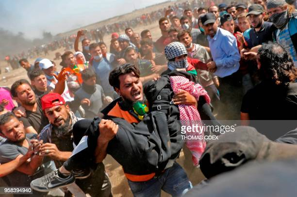 Palestinians carry a demonstrator injured during clashes with Israeli forces near the border between the Gaza strip and Israel east of Gaza City on...