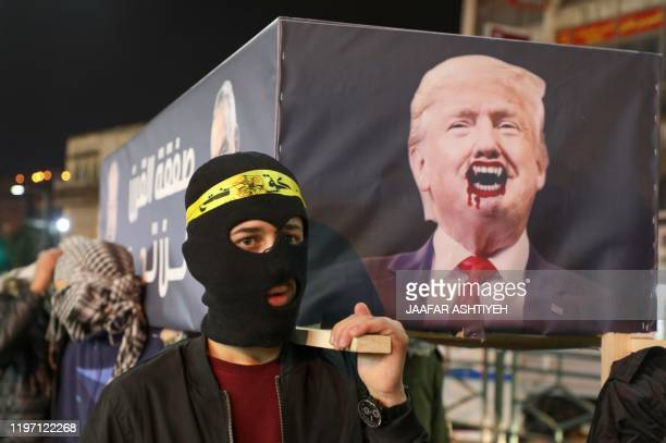 Palestinians carry a mock coffin bearing the portrait of US President Donald Trump during a demonstration in the West Bank city of Nablus on January...