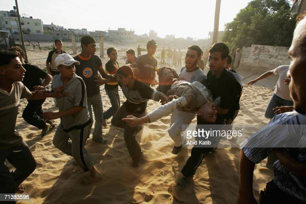 Palestinians carry a wounded man after Israeli troops opened fire on July 6 2006 in Beit Lahia northern Gaza Strip Israeli infantry and armor...