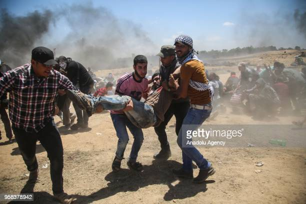 Palestinians carry a wounded man during a protest organized to mark 70th anniversary of Nakba also known as Day of the Catastrophe in 1948 and...