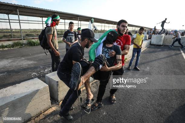 Palestinians carry a wounded protester from the site after Israeli forces intervene to protesters with tear gas canisters during an antioccupation...