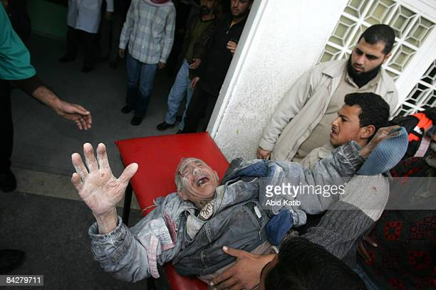 Palestinians carry an elderly man wounded in an Israeli military strike into Kamal Adwan hospital January 14 2009 in of Beit Lahia in the northern...