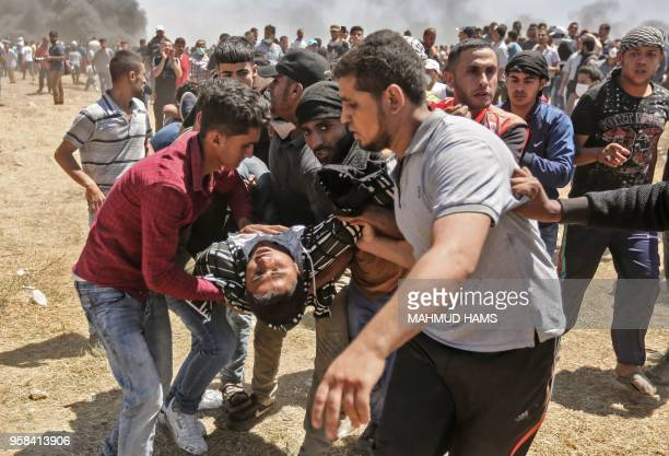 TOPSHOT Palestinians carry an injured man during clashes with Israeli forces near the border between the Gaza strip and Israel east of Gaza City on...