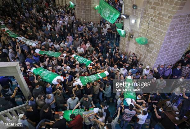 Palestinians carry the bodies of 13 Hamas militants, killed in Israeli air strikes, during their funeral at the al-Omari mosque in Gaza City, on May...