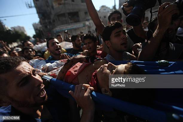 Palestinians carry the bodies of two boys from the Baker family whom medics said were killed with other two children from the same family by a shell...