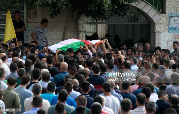 Palestinians carry the body of 48yearold mother of eight Aisha Rabi who died of her wounds after the car she was travelling in with her husband was...