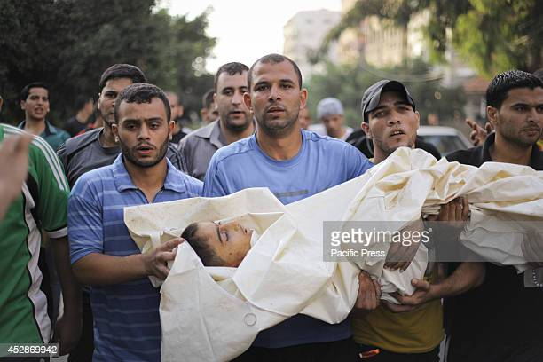 Palestinians carry the body of a boy after the raid by the Israeli army on the Shati refugee camp who was killed on impact, The Palestinian Ministry...