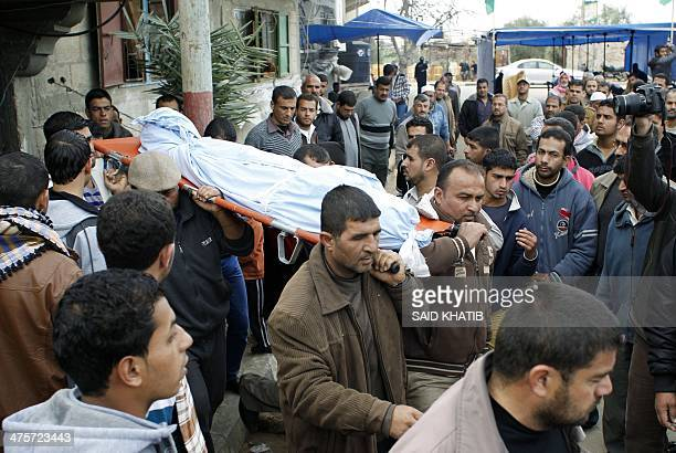 Palestinians carry the body of Amena Atiyyeh Qdeih a mentally ill Gazan woman who was shot dead by Israeli troops near the border early on March 1...