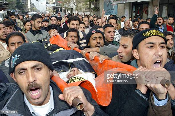 Palestinians carry the body of Fadi Abu-Kamr, who was shot dead by Israeli soldiers, during his funeral January 6, 2005 in Jabalya Refugee Camp, in...