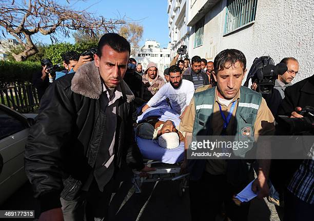 Palestinians carry the body of Ibrahim Mansour shot dead in the head by Israeli forces at a local hospital in Gaza City on February 13 2014 A...