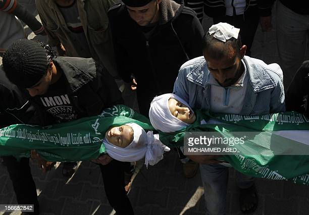 Palestinians carry the body of Jumana Abu Sefan 18 months and her brother Tamer three and a half years old during their funeral in the village of...