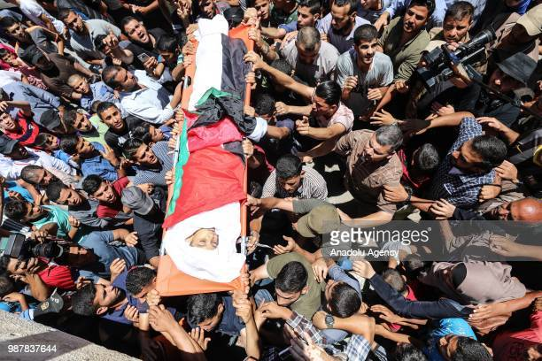 Palestinians carry the dead body of 13yearold Palestinian Yasser Abu alNaja who was killed by live Israeli bullets on Friday amid Palestinians'...