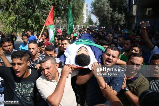 Palestinians carry the dead body of Ahmed Ibrahim Zaki alTaweel who was killed after Israeli soldiers intervened in 'Great March of Return'...