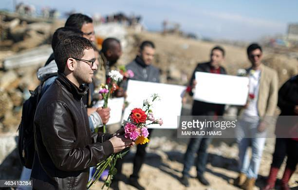 Palestinians carrying flowers gather at the sea of Gaza City on February 14 in remembrance of the three victims of the Chapel Hill shooting in the US...