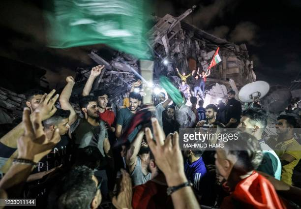 Palestinians celebrate in front of a destroyed building in Gaza City early on May 21 following a ceasefire brokered by Egypt between Israel and the...