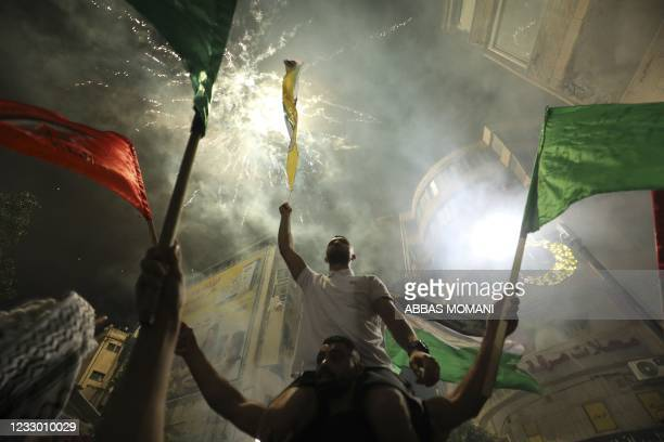 Palestinians celebrate in Ramallah city center in support of the resistance in Gaza, after the cease-fire between the Palestinians and Israel late in...