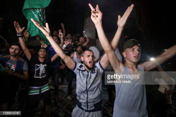 Palestinians celebrate in the streets following a ceasefire brokered by Egypt between Israel and the ruling Islamist movement Hamas, in Gaza City on...