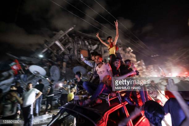 Palestinians celebrate the ceasefire brokered by Egypt between Israel and the the ruling Hamas Islamic movement in Gaza City on May 21, 2021. - A...