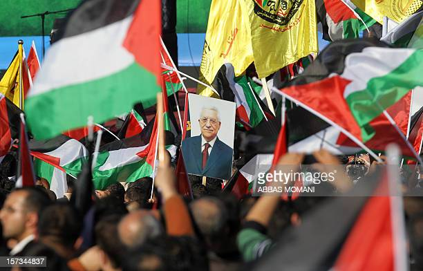 Palestinians celebrate waving their national flag as Palestinian president Mahmud Abbas delivers a speech to the crowd upon his arrival in the West...