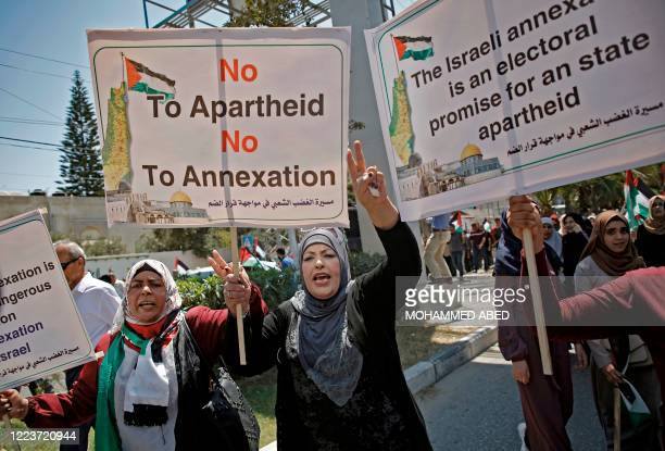 Palestinians chant and lift placards during a demonstration against Israel's West Bank annexation plans in Gaza City on July 1, 2020. - Expectations...
