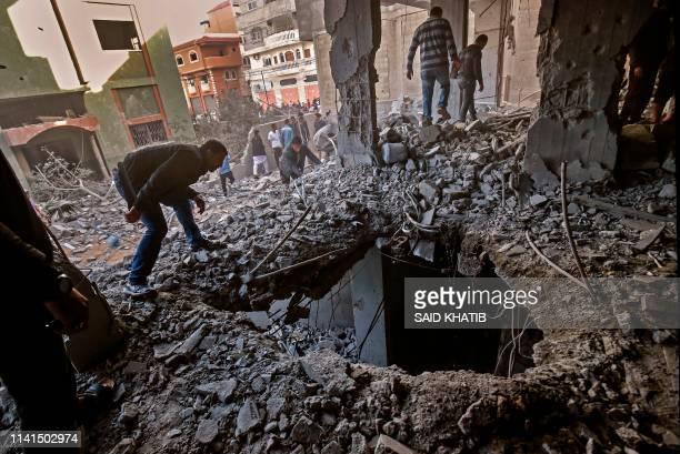 TOPSHOT Palestinians check the damage in a destroyed building following Israeli airstrikes targeting Rafah in the southern Gaza Strip on May 5 2019...