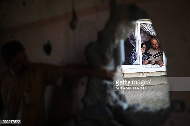 TOPSHOT Palestinians check the damage in their house after it was hit by Israeli tank fire on September 6 2016 in Beit Hanun in the northern Gaza...