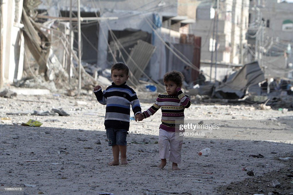 Palestinians children walk past destroyed buildings following Israeli air strikes on the southern Gaza Strip town of Rafah on November 18, 2012. Israeli war planes hit a Gaza City media centre and homes in northern Gaza in the early morning, as the death toll mounted, despite suggestions from Egypt's President Mohamed Morsi that there could be a 'ceasefire soon.'