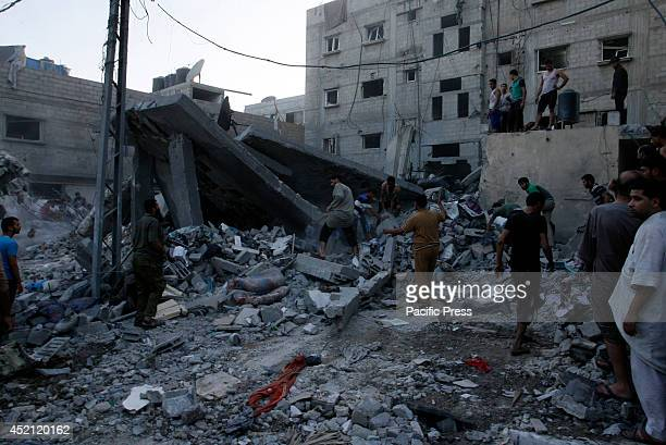 Palestinians civil defense personnel examine the rubble of a house after it was targeted in an air raid on Rafah, in the south of Gaza strip. Five...